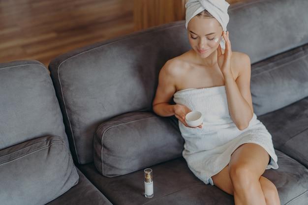 Vue de dessus de la belle jeune femme détendue est assise sur un canapé confortable applique de la crème sur son visage
