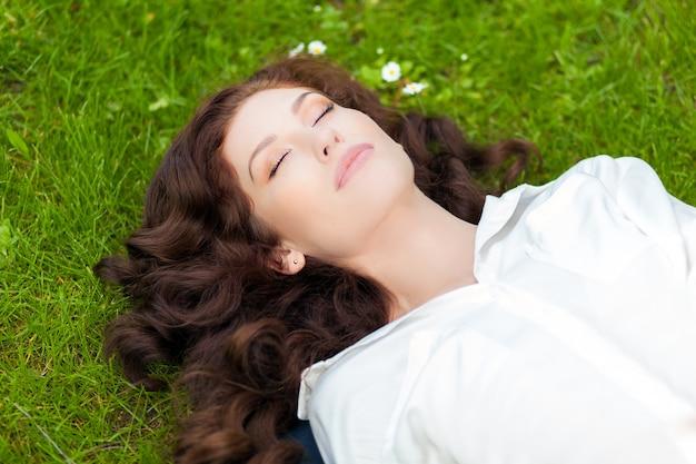 Vue de dessus d'une belle jeune femme dormant sur l'herbe