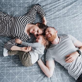 Vue de dessus de la belle jeune mère, père et leur fille regardant la caméra et souriant en position couchée sur le lit tête à tête