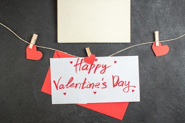 Vue de dessus belle note joyeuse saint valentin note sur fond sombre amour couple sentiments mariage présent coeur couleur