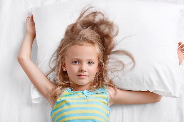 Vue de dessus de la belle petite belle enfant de sexe féminin aux cheveux clairs, vêtue de pyjama rayé, se trouve sur l'oreiller, se repose bien au lit