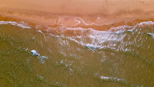 Vue de dessus de la belle plage de sable avec vue sur la propagation des vagues d'eau de mer turquoise depuis le concept d'été de la caméra drone photo de haute qualité