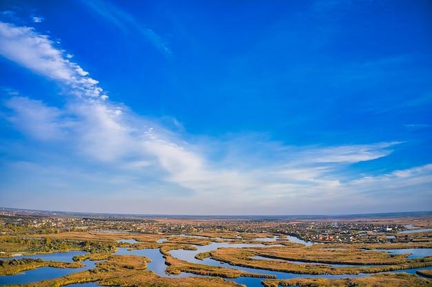 Vue de dessus de la belle samarskie plavni sur le dniepr avec un village à proximité dans la chaude lumière du soir. vue aérienne