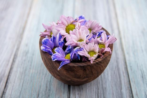 Vue de dessus de belles fleurs de marguerite colorées sur un bol en bois sur un fond en bois gris