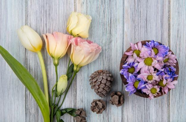 Vue de dessus de belles fleurs de marguerite colorées sur un bol en bois avec des pommes de pin et tulipe blanche sur un fond en bois gris