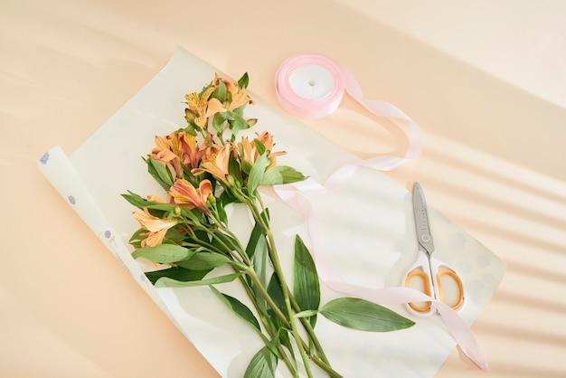 Vue de dessus de belles fleurs oranges, ciseaux, ruban et papier kraft sur la surface du papier