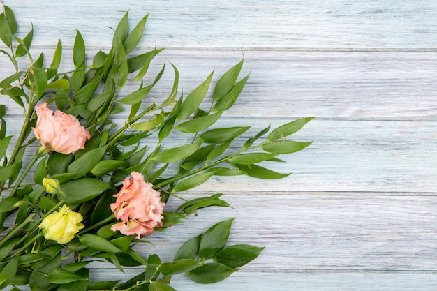 Vue de dessus de belles fleurs telles que des pivoines roses et des roses jaunes avec des feuilles vertes sur bois avec espace copie