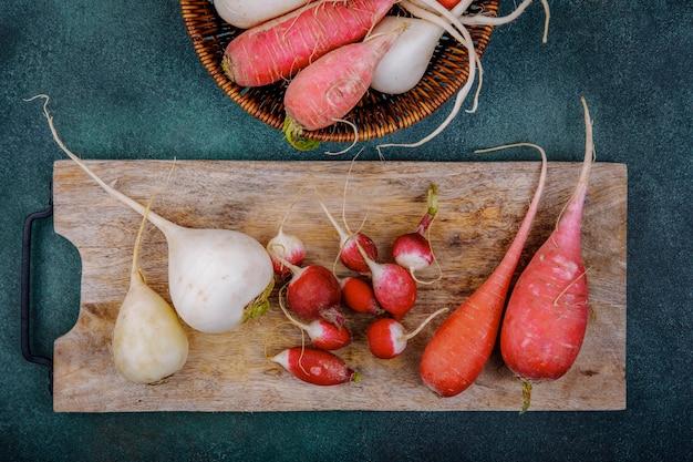 Vue de dessus des betteraves légumes racines rouge rosé et blanc sur une planche de cuisine en bois avec des radis sur une surface verte