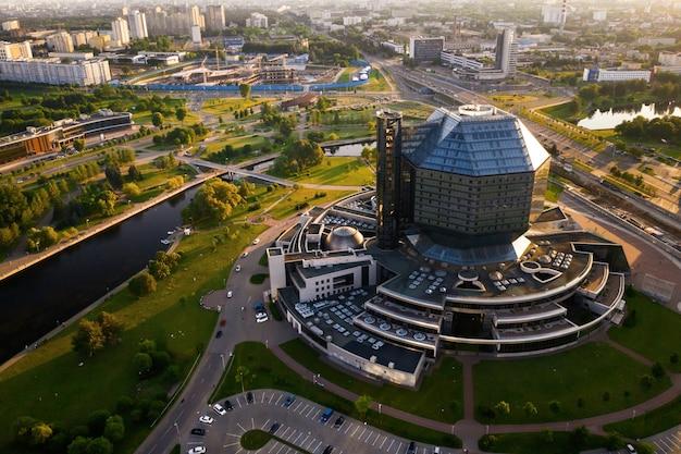 Vue de dessus de la bibliothèque nationale et d'un nouveau quartier avec un parc à minsk-la capitale de la république du bélarus au coucher du soleil, un bâtiment public