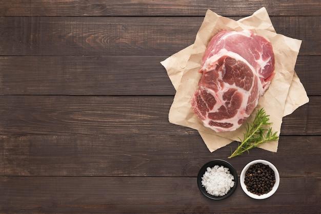 Vue de dessus bifteck de porc cru et ail, poivre sur fond de bois