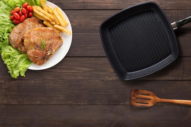 Vue de dessus de bifteck de porc, poêle à griller et spatule sur le fond en bois. copyspace pour votre texte
