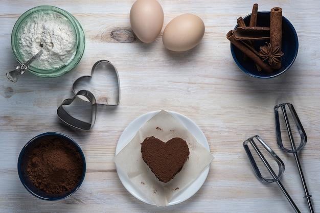 Vue de dessus d'un biscuit dessert au chocolat en forme de coeur allongé sur une soucoupe à côté de formes de fer, paupières, bâtons de cannelle et autres ingrédients sur un fond en bois blanc