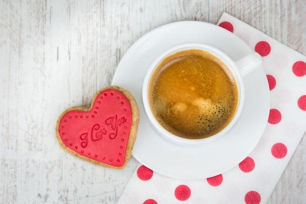 Vue de dessus d'un biscuit en forme de coeur et d'une tasse de café.