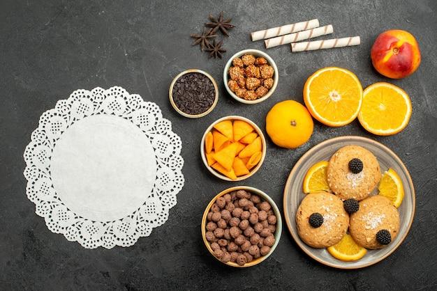 Vue de dessus des biscuits au sable avec des tranches d'orange sur une surface gris foncé biscuits aux fruits sucrés thé