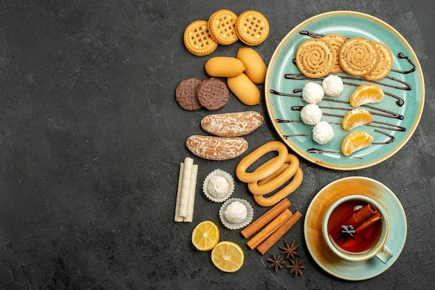 Vue de dessus des biscuits au sucre avec des bonbons tasse de thé sur fond gris