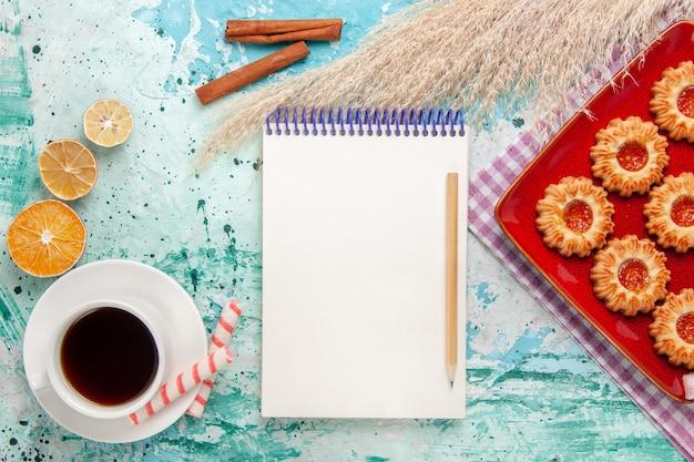 Vue de dessus biscuits au sucre à l'intérieur de la plaque rouge avec une tasse de thé sur le fond bleu