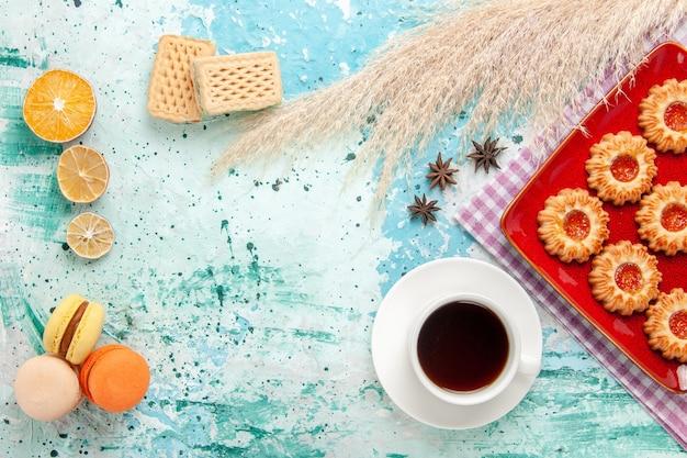 Vue de dessus biscuits au sucre à l'intérieur de la plaque rouge avec tasse de thé et macarons sur fond bleu clair