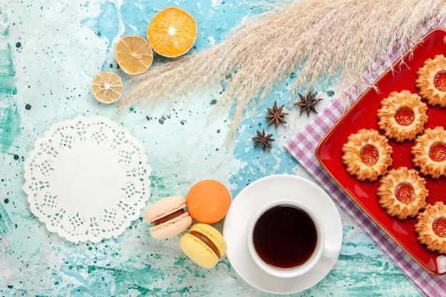 Vue de dessus biscuits au sucre à l'intérieur de la plaque rouge avec tasse de thé et macarons sur fond bleu