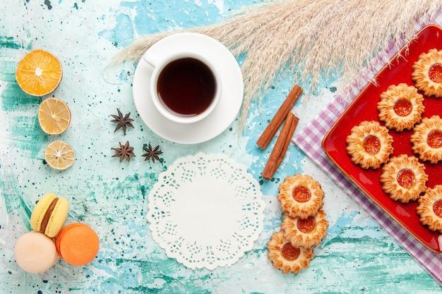 Vue de dessus biscuits au sucre à l'intérieur de la plaque rouge avec tasse de thé et macarons français sur fond bleu