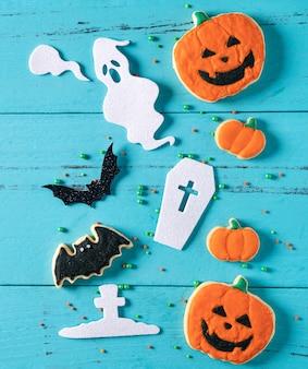 Vue de dessus des biscuits au sucre de pain d'épice au glaçage décoré de fête d'halloween sur fond bleu avec espace de copie et mise à plat.