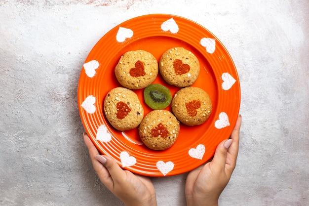 Vue de dessus des biscuits au sucre rond à l'intérieur de la plaque sur une surface blanche biscuit biscuit pâte à thé gâteau sucré