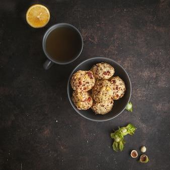 Vue de dessus des biscuits aux pistaches dans un bol avec une tasse de café et de citron alignés en diagonale sur une texture brun foncé.