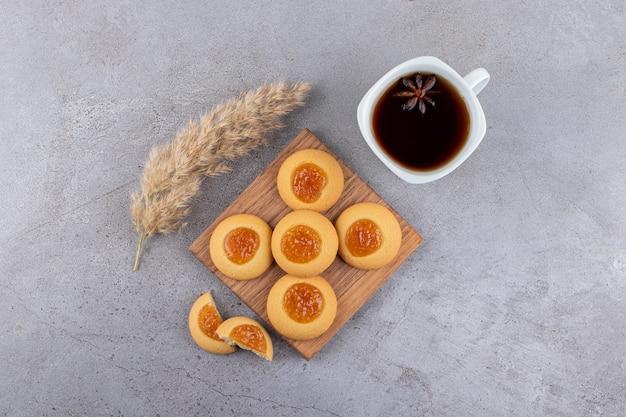 Vue de dessus des biscuits faits maison avec de la confiture et une tasse de thé.