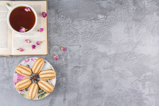 Vue de dessus des biscuits faits maison avec tasse de thé pf et livre sur gris.