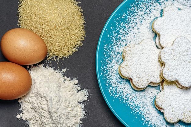 Vue de dessus des biscuits en forme de fleur dans une assiette bleue, à côté des œufs, de la farine et de la cassonade