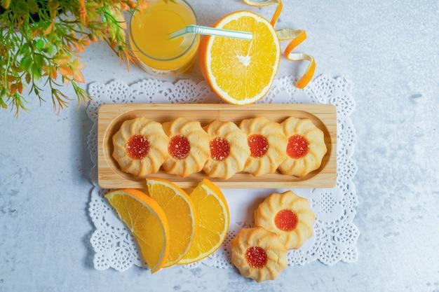 Vue de dessus de biscuits frais faits maison avec de la confiture et des tranches d'orange sur un mur gris.