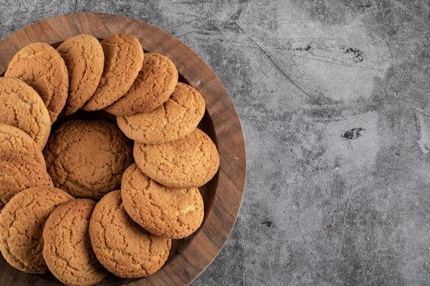 Vue de dessus de biscuits frais faits maison sur un plateau en bois.
