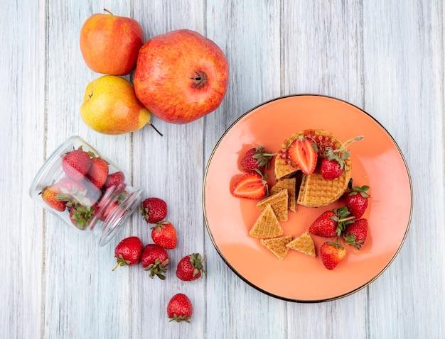 Vue de dessus des biscuits gaufres et des fraises en assiette avec des fraises débordant de pot et pomme grenade poire sur la surface en bois