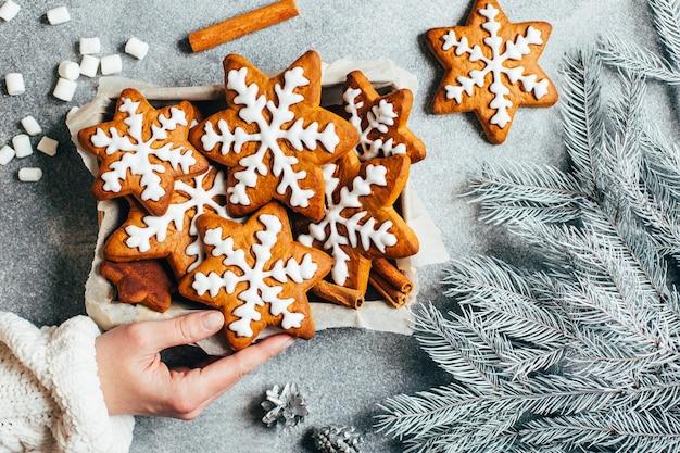 Vue de dessus des biscuits de pain d'épice glacés de noël dans une boîte dans une main féminine sur fond gris