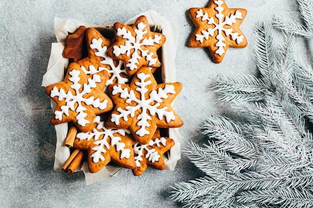 Vue de dessus des biscuits de pain d'épice de noël sous forme de flocons de neige avec du glaçage à côté des branches d'un arbre de noël sur fond gris