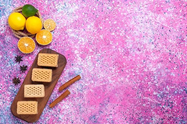 Vue de dessus des biscuits sandwich gaufres avec garniture de crème aux fruits et thé sur la surface rose clair