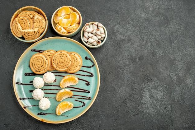 Vue de dessus des biscuits sucrés avec des bonbons à la noix de coco sur le fond gris