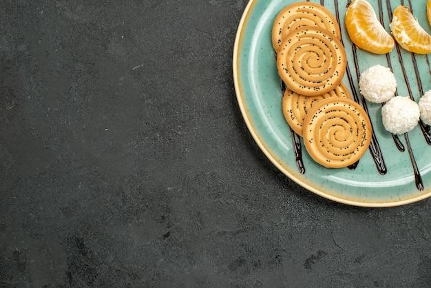 Vue de dessus des biscuits sucrés avec des bonbons à la noix de coco à l'intérieur de la plaque sur un bureau gris