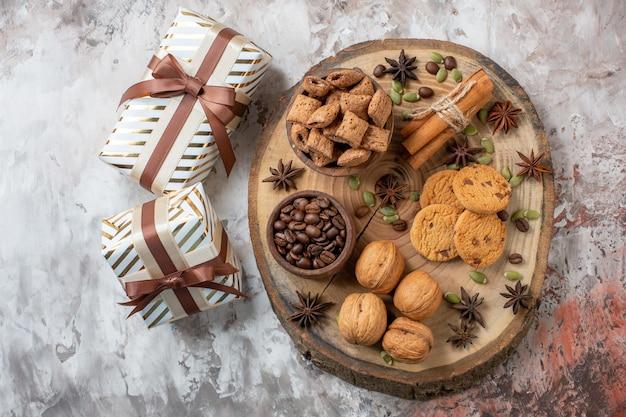 Vue de dessus des biscuits sucrés avec des cadeaux et des noix sur une table lumineuse