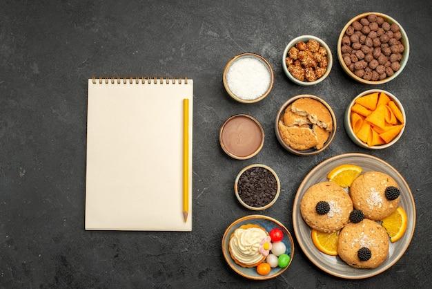 Vue de dessus des biscuits sucrés avec des chips et des tranches d'orange sur une surface sombre biscuits fruti biscuit tarte sucrée