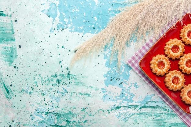 Vue de dessus des biscuits sucrés avec de la confiture orange sur fond bleu