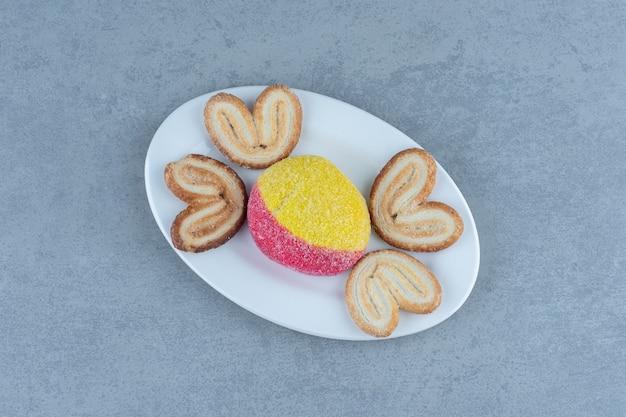 Vue de dessus des biscuits sucrés faits maison sur une plaque blanche.