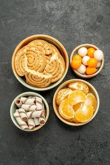 Vue de dessus des biscuits sucrés avec des fruits et des bonbons sur le fond sombre