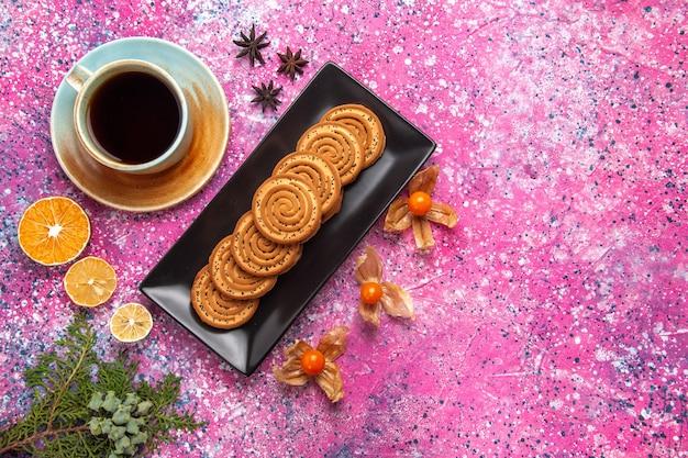 Vue de dessus de biscuits sucrés à l'intérieur de forme noire avec une tasse de thé sur une surface rose clair