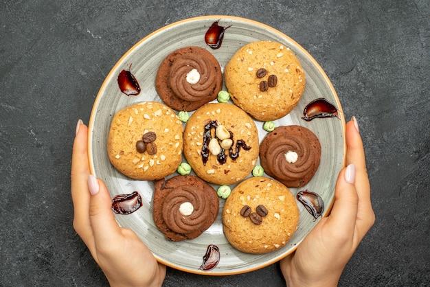 Vue de dessus biscuits sucrés à l'intérieur de la plaque sur fond gris foncé biscuit au sucre biscuit sucré gâteau thé