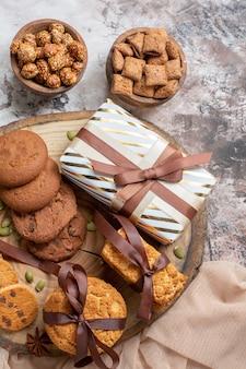 Vue de dessus des biscuits sucrés avec des noix et des cadeaux sur une table lumineuse