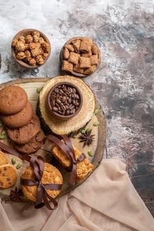 Vue de dessus des biscuits sucrés avec des noix et une tasse de café sur un sol clair