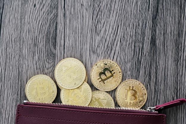 Vue de dessus des bitcoins dorés sur le portefeuille en cuir rouge