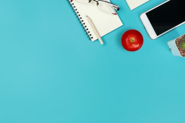 Vue de dessus bleu bureau pastel avec ordinateur et pomme