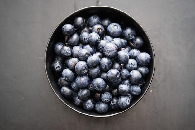 Vue de dessus de bleuets fraîchement cueillis dans un bol noir
