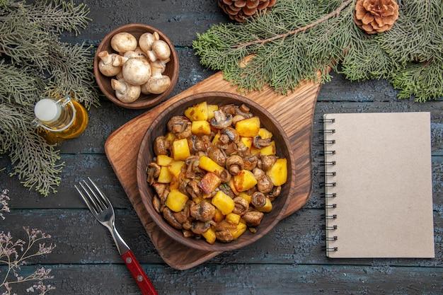 Vue de dessus et bloc-notes pommes de terre et champignons dans un bol sur une planche à découper à côté de la fourchette et du bloc-notes sous un bol d'huile de champignons en bouteille et des branches avec des cônes
